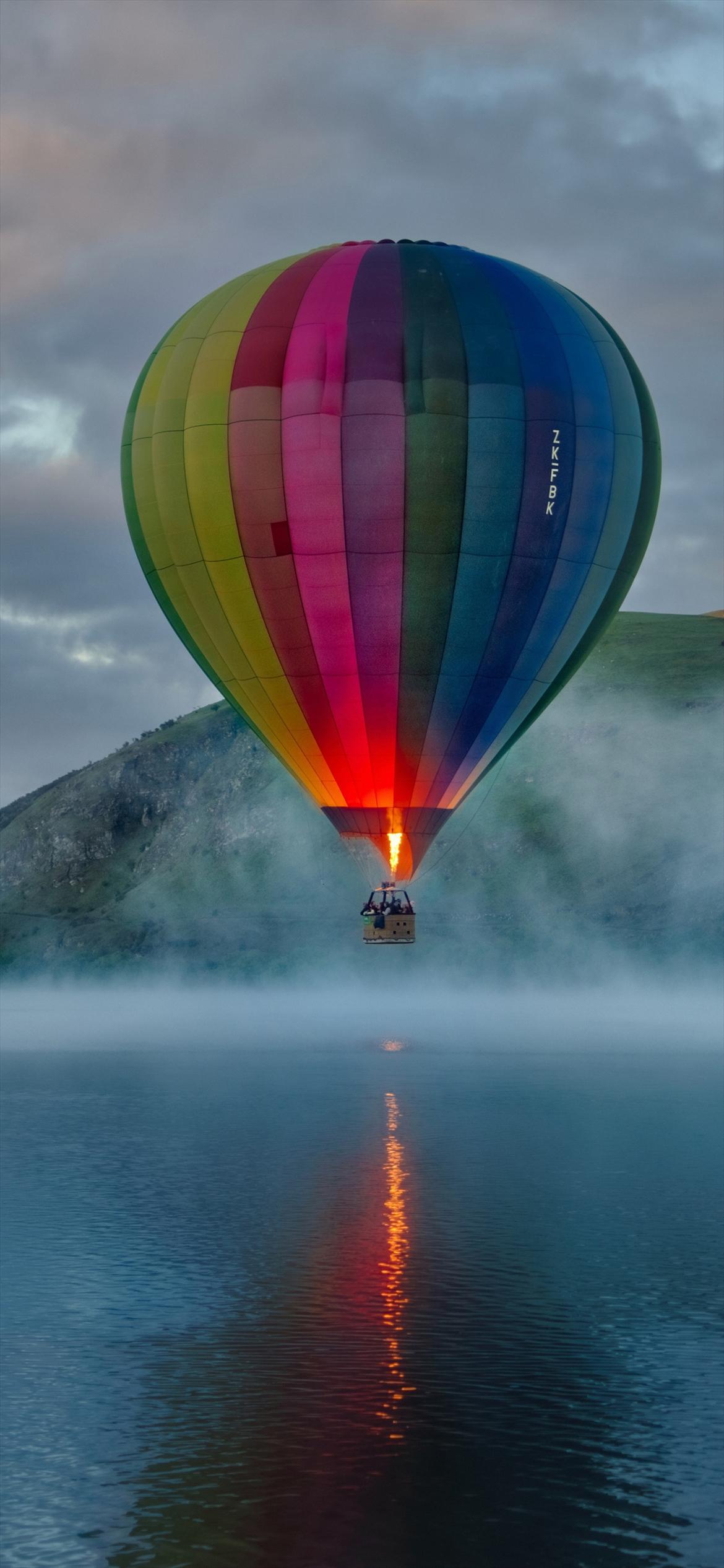海の上を飛ぶカラフルな気球 iPhone 13 Pro 壁紙・待ち受け