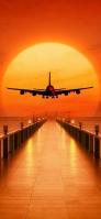 滑空する飛行機と夕日 iPhone 11 Pro スマホ壁紙・待ち受け