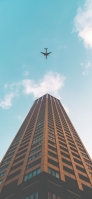 茶色の高層ビルと青空と飛行機 iPhone 12 Pro スマホ壁紙・待ち受け