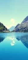 澄んだ青空と緑残る岩山と綺麗な湖 iPhone 12 Pro スマホ壁紙・待ち受け
